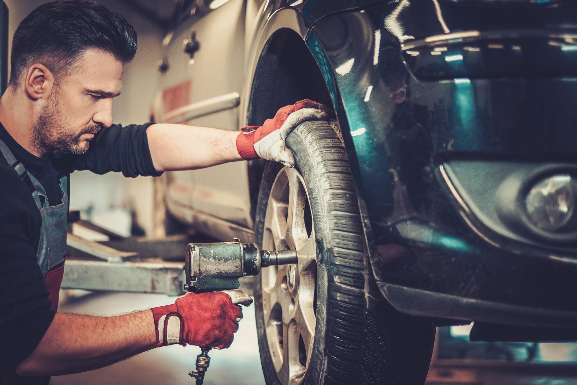 Professional car mechanic changing car wheel in auto repair service.